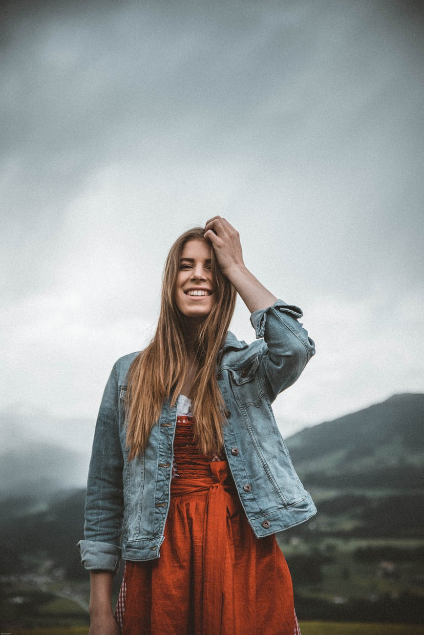 woman wearing blue denim button up jacket under heavy clouds